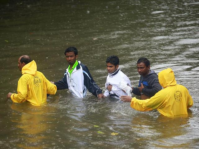 People are helped by police personnel as they cross a flooded road during heavy rains in Mumbai (Reuters Photo)