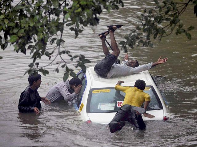 People-wade-through-a-water-logged-road-after-heavy-rains-near-Dadar-in-Mumbai-PTI-Photo