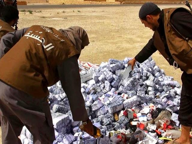 In-this-photo-released-on-May-3-2015-by-a-militant-website-members-of-the-Islamic-State-group-s--vice-police-known-as-Hisba-prepare-to-burn-cigarettes-and-alcohol-in-Homs-Province-Syria-AP-Photo