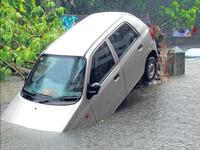 A-car-gets-lifted-off-the-ground-after-a-tree-near-which-it-was-parked-was-uprooted-at-King-s-Circle-in-Mumbai-following-hevay-rains-in-Mumbai-Vijayanand-Gupta-HT-Photo