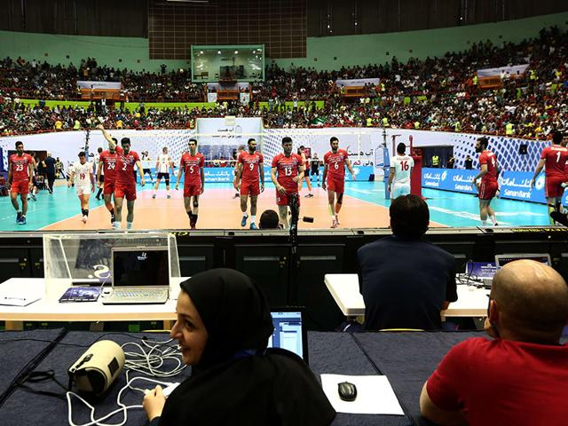 An-Iranian-employee-of-Iran-s-volleyball-federation-smiles-as-Iranian-players-warm-up-before-the-volleyball-match-Iranian-authorities-had-denied-women-ticket-holders-entry-to-the-match-AFP-Photo