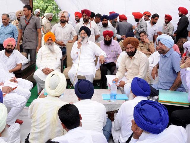 PAFC-chairman-and-loan-defaulter-Dyal-Singh-Kolianwali-orange-turban-sitting-on-the-left-side-of-Punjab-chief-minister-Parkash-Singh-Badal-at-a-sangat-darshan-programme-in-a-Lambi-village-in-Bathinda-on-Monday-Sanjeev-Kumar-HT
