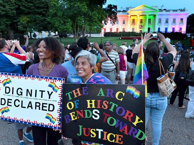 Gay-activists-hold-signs-in-front-of-the-White-House-lightened-in-the-rainbow-colors-in-Washington-The-US-Supreme-Court-ruled-that-gay-marriage-is-a-nationwide-right-a-landmark-decision-in-one-of-the-most-keenly-awaited-announcements-in-decades-and-sparking-scenes-of-jubilation-AFP-Photo