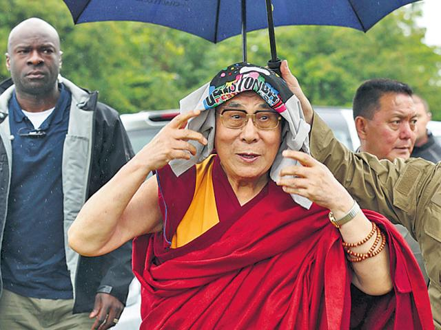 The-Dalai-Lama-wears-a-Glastonbury-Festival-T-shirt-on-his-head-as-he-arrives-in-rain-in-Somerset-England-on-Sunday-AP-Photo
