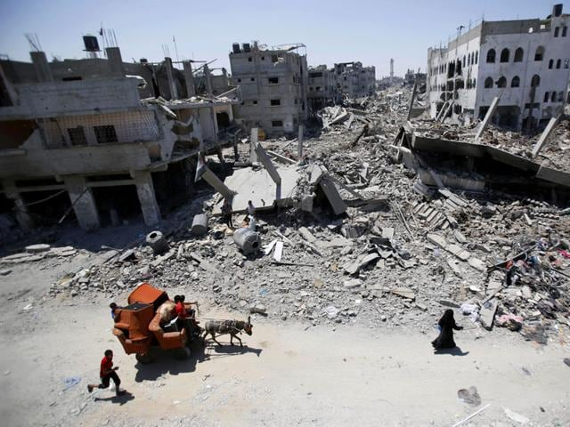 Palestinians-carry-their-belongings-through-the-heavily-bombed-Gaza-City-neighborhood-of-Shijaiyah-close-to-the-Israeli-border-AP-File-Photo