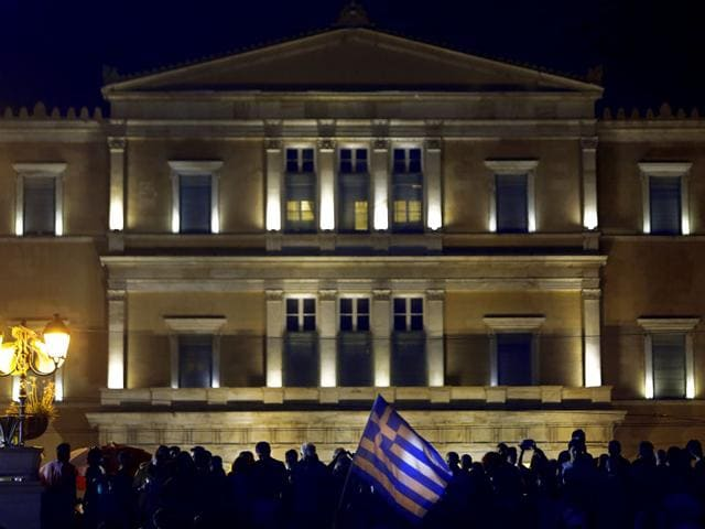 A-supporter-of-a-No-vote-in-the-upcoming-referendum-waves-a-Greek-flag-in-front-of-the-Parliament-during-a-rally-at-Syntagma-square-in-Athens-AP-Photo