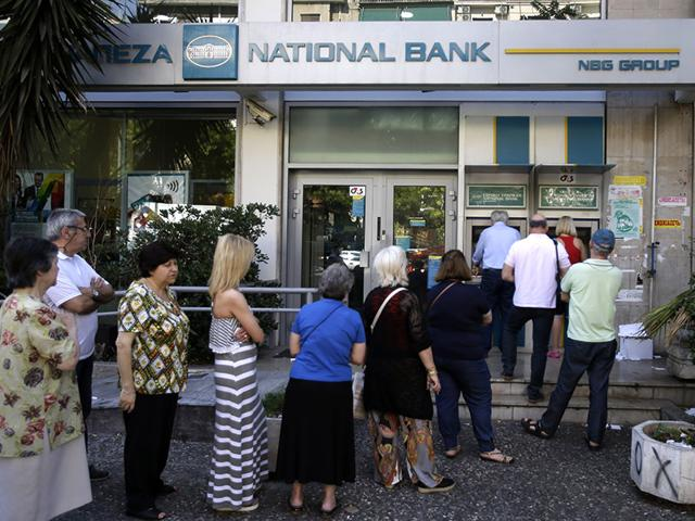 People-stand-in-a-queue-to-use-an-ATM-outside-a-closed-bank-next-to-a-sign-on-the-plant-bottom-right-reading-NO-in-Athens-AP-Photo
