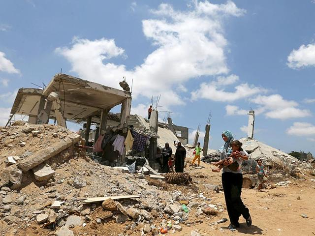 A-Palestinian-woman-holds-her-daughter-as-she-walks-past-the-ruins-of-houses-that-witnesses-said-were-destroyed-by-Israeli-shelling-during-a-50-day-war-last-summer-Reuters-File-Photo