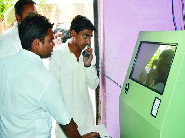 Jail-inmates-make-a-call-at-a-telephone-kiosk-and-below-police-officials-work-on-the-e-prison-software-HT-photos