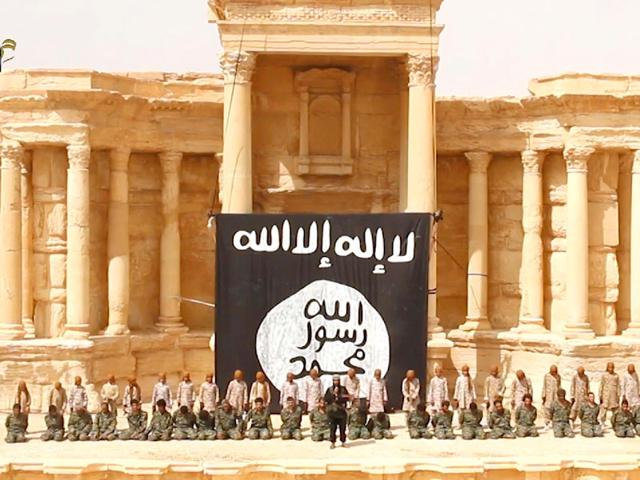 An-image-grab-taken-from-a-video-made-available-by-a-Jihadist-media-outlet-allegedly-shows-25-Syrian-government-soldiers-kneeling-in-front-of-what-appears-to-be-children-or-teenagers-wearing-desert-camouflage-in-the-ancient-amphitheatre-in-the-city-of-Palmyra-ahead-of-being-executed-AFP-Photo