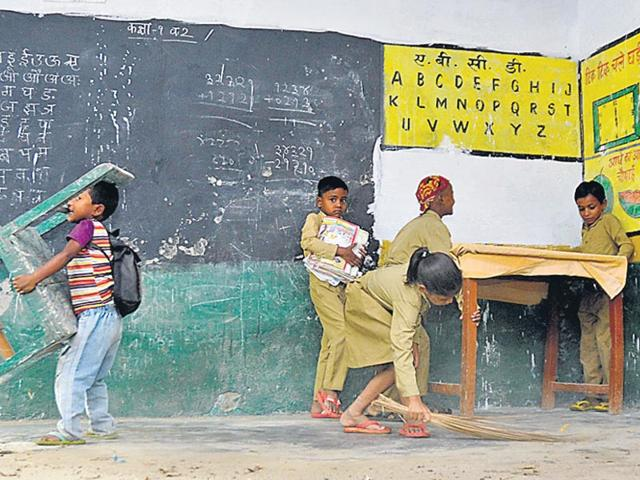 A-student-in-a-Lucknow-school-sweeps-the-classroom-while-others-adjust-the-furniture-Deepak-Gupta-HT-Photos