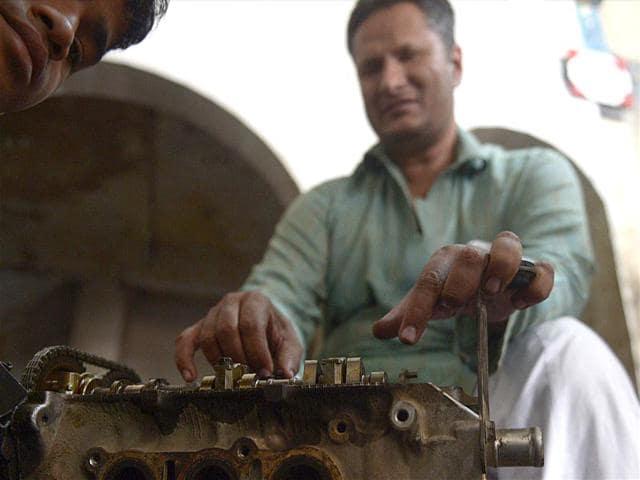Blind-mechanic-Asif-Patel-works-on-a-car-engine-at-his-workshop-in-Karachi-AFP-Photo