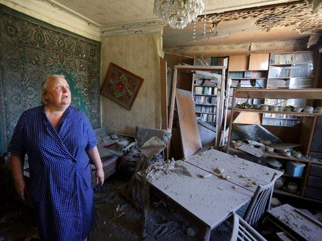 A woman assesses the damages to her house as a result of shelling between Ukrainian forces and pro-Russian separatists in the eastern Ukrainian city of Donetsk on Sunday. (AFP Photo)