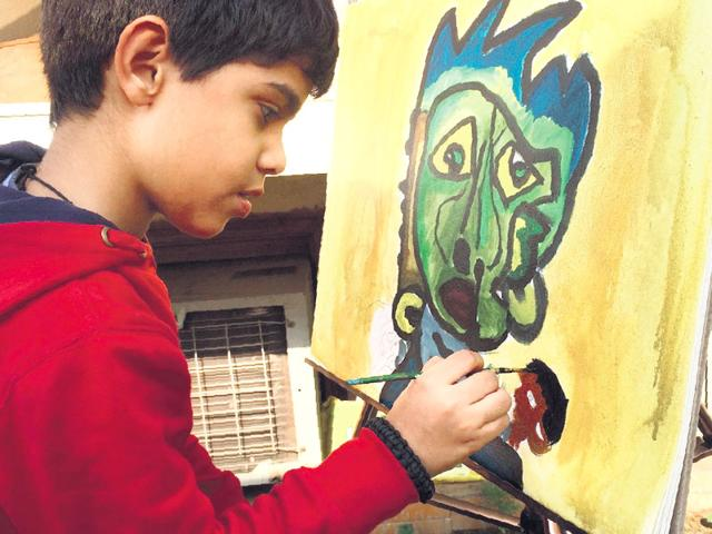 Aarav Verma live paints one of his artworks that will be displayed at the exhibition.