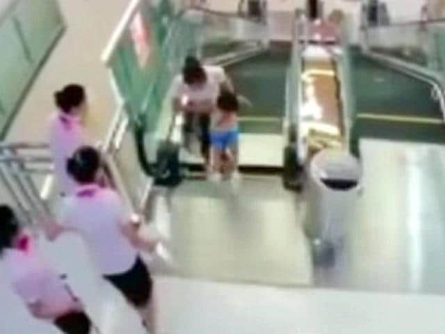 An-image-from-CCTV-camera-showing-Xiang-Liujuan-and-her-son-as-a-panel-at-the-top-of-the-escalator-gave-way-Reuters