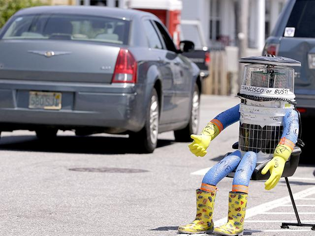 A-car-drives-by-HitchBOT-a-hitchhiking-robot-in-Marblehead-Massachusetts-AP-File-Photo