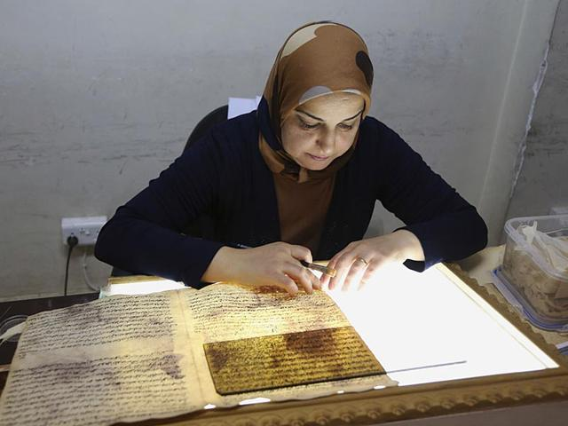 A-member-of-the-library-restoration-staff-works-on-a-damaged-document-at-the-Baghdad-National-Library-in-Iraq-Librarians-and-academics-in-Baghdad-are-working-to-preserve-what-s-left-after-thousands-of-documents-were-lost-or-damaged-at-the-height-of-the-US-led-invasion-As-the-Islamic-State-militants-now-set-out-to-destroy-Iraq-s-history-and-culture-a-major-preservation-and-digitization-project-is-underway-in-the-capital-to-safeguard-a-millennia-worth-of-history-AP-Photo