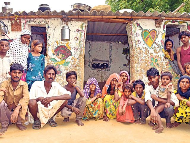 Family-members-of-Raju-Lohar-outside-their-dilapidated-hut-along-with-grieving-family-members-and-relatives-in-Vatika-village-on-Monday-Prabhakar-Sharma-HT-Photo
