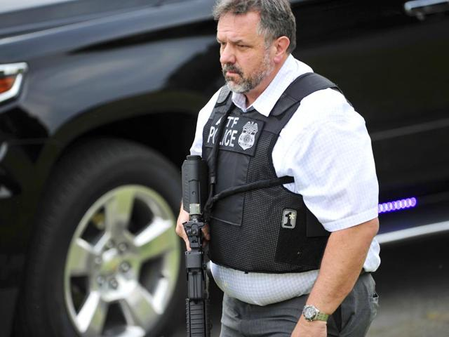 A-police-officer-walks-on-the-scene-of-a-reported-shooting-in-Nashville-Tennessee-A-suspect-wielding-a-hatchet-and-a-gun-inside-a-Nashville-area-movie-theater-died-after-exchanging-gunshots-with-a-police-team-that-stormed-the-theater-AP-Photo