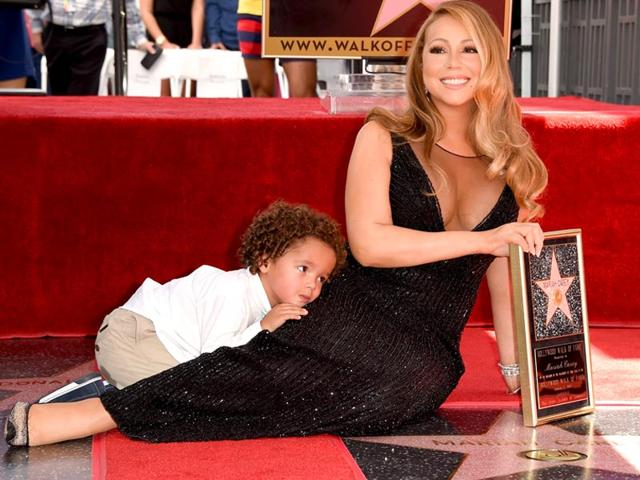 Mariah Carey's son Moroccan Cannon clings to his famous mom as she is honoured with a star on The Hollywood Walk of Fame. (AFP)
