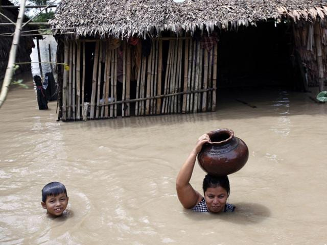A-woman-carries-a-water-pot-on-her-head-as-she-and-her-child-wade-through-near-their-half-submerged-house-in-Nyaung-Tone-Ayeyarwaddy-Delta-about-60-miles-southwest-of-Yangon-Myanmar-AP-Photo