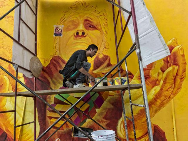 """An artist nicknamed """"Trejo"""" paints a mural honouring the wisdom of elderlies at one of the streets of the hill 'Las Palmitas' in Pachuca, Hidalgo state, Mexico. (AFP Photo)"""