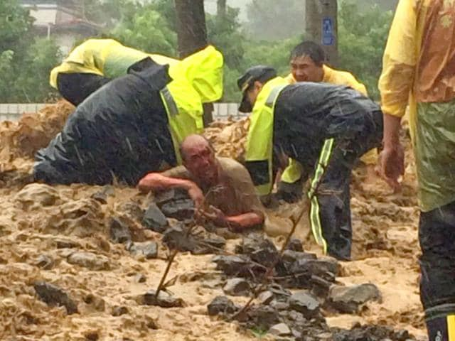 This-handout-picture-taken-on-August-8-2015-by-the-New-Taipei-City-Fire-Department-shows-rescue-personnel-extricating-a-man-from-mud-and-rubble-in-Wulai-New-Taipei-City-as-typhoon-Soudelor-hit-Taiwan--Typhoon-Soudelor-moved-towards-China-August-9-AFP-PHOTO-New-Taipei-City-Fire-Department