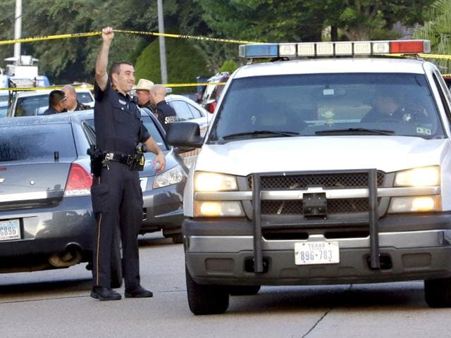 A-member-of-the-Harris-County-Sheriff-s-Department-raises-the-crime-scene-tape-for-a-vehicle-outside-the-scene-of-shooting-where-eight-people-were-found-dead-AP-Photo