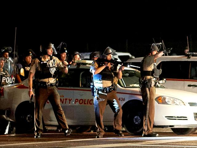 A-St-Louis-County-police-officer-directs-an-oncoming-car-looking-to-evacuate-the-area-after-a-police-involved-shooting-during-a-protest-march-on-August-9-2015-on-West-Florissant-Avenue-in-Ferguson-AFP-Photo