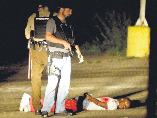 Police-stand-near-a-suspect-in-a-parking-lot-after-gunfire-during-a-protest-on-the-anniversary-of-the-death-of-Michael-Brown-on-Sunday-AP-Photo