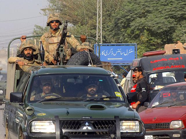 Pakistan army troops rush towards an air force base in Peshawar, Pakistan. (AP Photo)