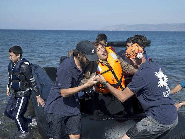 Volunteers help an Afghan woman after she arrived aboard a dinghy from Turkey, to the island of Lesbos, Greece. A girl, about five-years-old died and at least 13 undocumented refugees and migrants were missing after a boat overturned off Lesbos island. (AP Photo)