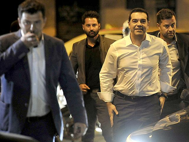 Leader of the left-wing Syriza party and former Prime Minister Alexis Tsipras surrounded by his security arrives at the headquarters of his party in Athens, Sunday, Sept. 20, 2015. Tsipras appeared poised for victory in Greece's early election Sunday, but falling short of an absolute majority needed to form a government. (AP Photo)