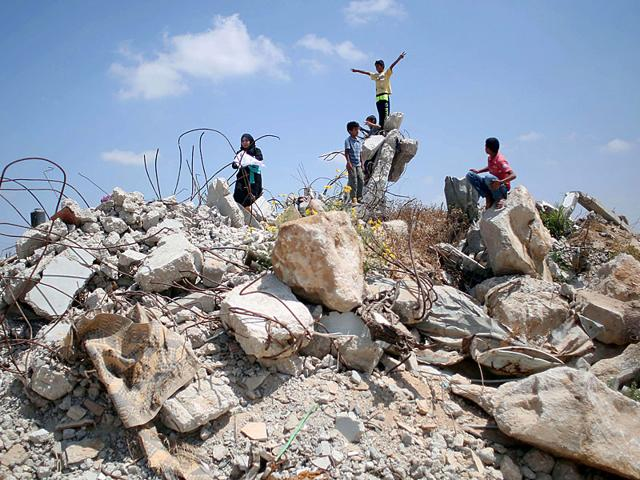 Palestinian children play in the rubble of houses destroyed during the 50-day war between Israel and Hamas militants in 2014. (AFP Photo)