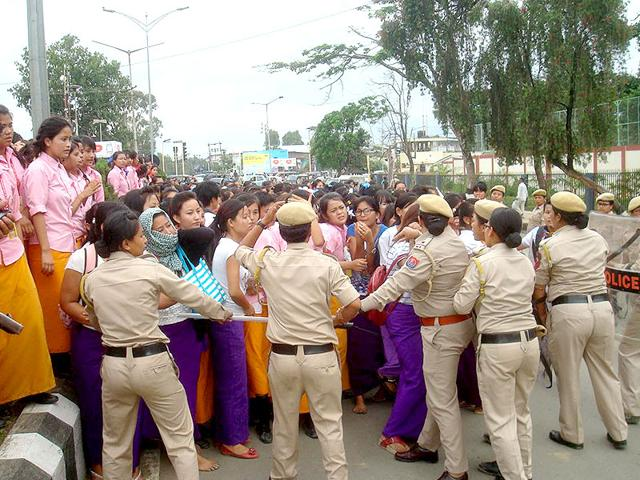 Police try to intercept a protest march by students of TG Higher Secondary School and GP Women college in front of Raj Bhavan in Imphal. (Sobhapati Samom/HT Photo)