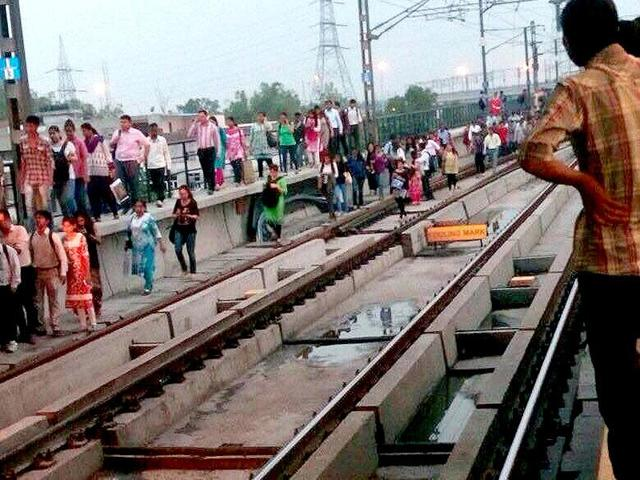 Passengers cross metro tracks after services were disrupted when a Blue Line train developed a technical snag. (HT Photo)