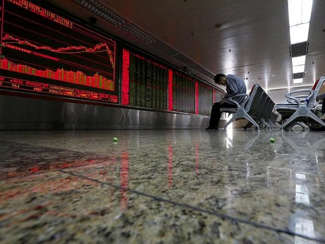 An investor takes notes as he watches a board showing stock prices at a brokerage office in Beijing, China. (Reuters File Photo)