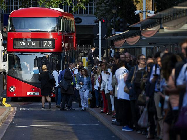 Early morning commuters form queues to board buses at Victoria station during a tube strike in London on July 9, 2015. London's roads, buses and overland trains struggled to cope in Thursday's morning rush hour as commuters battled into work in the face of London Underground's first strike shutdown since 2002. (AFP PHOTO)