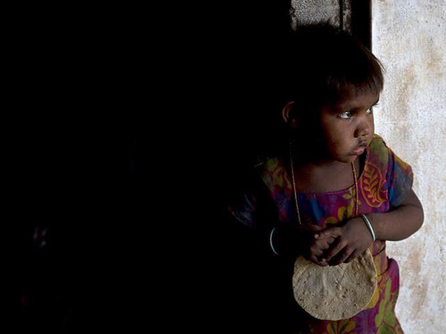 A girl holds a chapati in her hand, served as a part of mid-day meal programme, at Madkheda, Madhya Pradesh. (AP Photo)