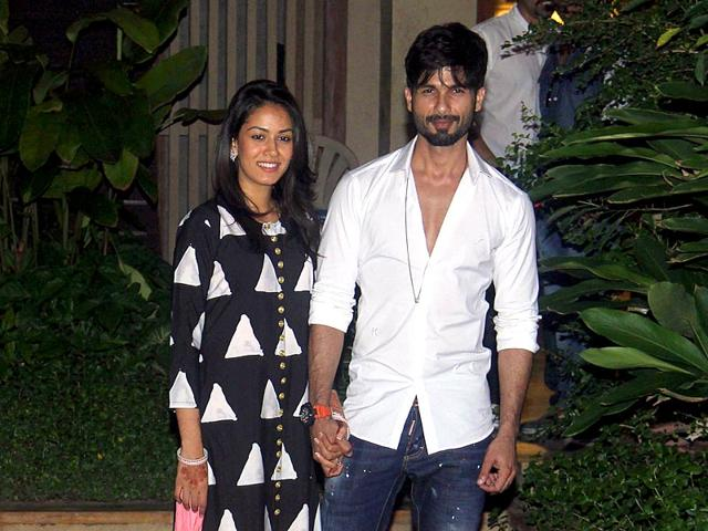 Mira and Shahid Kapoor pose for images as they reach their Mumbai residence after their Delhi wedding. (PTI photo)
