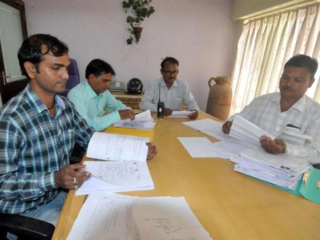 Education department officials at SICA School verify RTE forms of students in Indore on Wednesday. (Arun Mondhe/HT photo)