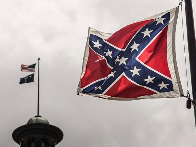 A-Confederate-flag-is-held-up-by-a-man-at-a-rally-outside-the-State-House-to-get-the-Confederate-flag-removed-from-the-grounds-in-Columbia-South-Carolina-Reuters-Photo
