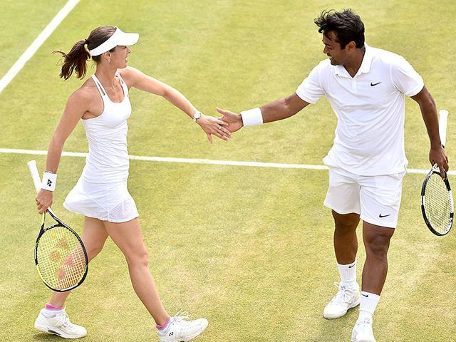 Switzerland's Martina Hingis (L) and her partner India's Leander Paes beat top seeds Mike Bryan and Bethanie Mattek Sands of the United States 6-3, 6-4 on July 10, 2015 to enter the mixed doubles final of the 2015 Wimbledon Championships at The All England Lawn Tennis and Croquet Club in London. (AFP Photo)