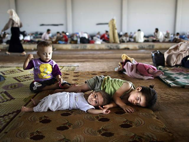 Syrian children who fled their home with their family take refuge at the Bab Al-Salameh border crossing, in hopes of entering one of the refugee camps in Turkey, near the Syrian town of Azaz. (AP File Photo)
