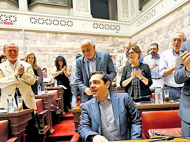 Greek PM Alexis Tsipras is applauded by lawmakers before addressing his parliamentary group meeting at the Greek Parliament in Athens on Friday. (Reuters Photo)