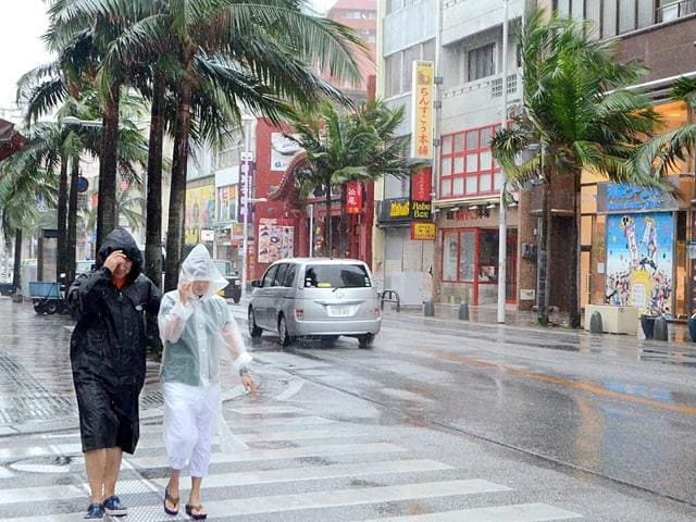 People walk on the street under heavy rain and winds caused by Typhoon Chan-hom in Naha, Okinawa Prefecture. (AFP Photo)
