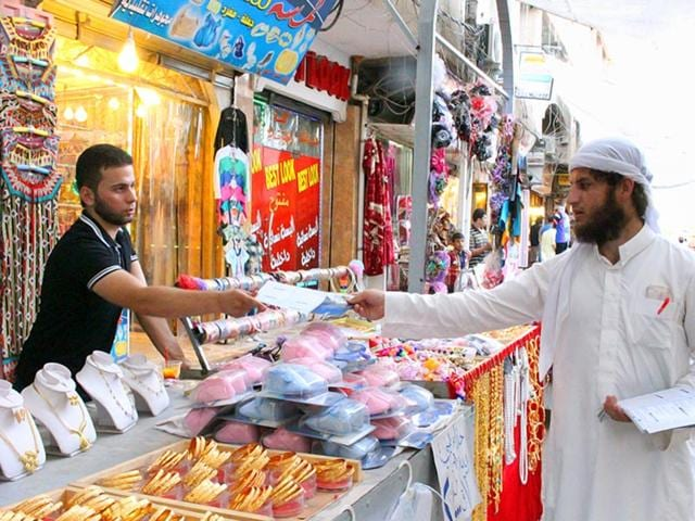In this photo provided by a website of the Islamic State group, an IS member, right, distributes pamphlets about fasting before Ramzan in Mosul, northern Iraq. (AP Photo)