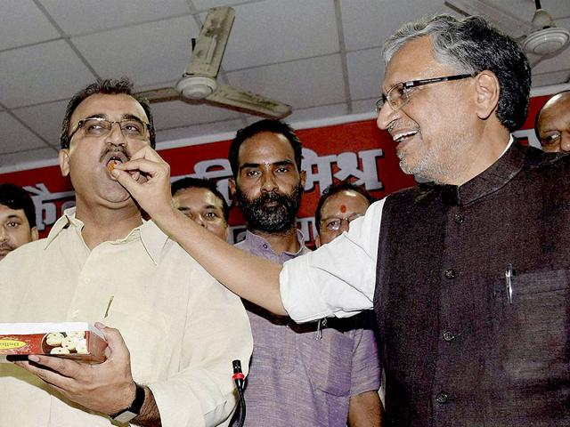BJP senior leader Sushil Kumar Modi offers sweet to state party president Mangal Pandey and opposition leader Nand Kishor Yadav after National Democratic Alliance's victory in the Bihar Legislative Council elections in Patna on Friday. (PTI Photo)
