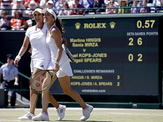 Martina Hingis of Switzerland, right, celebrates with partner Sania Mirza of India after winning their women's doubles semi-final match of the 2015 Wimbledon Championships against Raquel Kops-Jones and Abigail Spears of the United States, at The All England Lawn Tennis and Croquet Club in London, on July 10, 2015. Hingis and Mirza won 6-1, 6-2. (AP Photo)