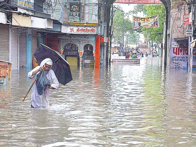 A man wades through an inundated market place in Sikar after the heavy showers on Thursday (HT Photo)